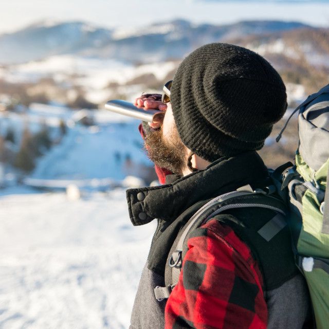"""Man drinking from a hip flask on a hiking trip"" stock image"