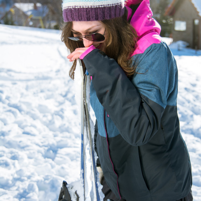 """""""girl laughing and holding a pair skis"""" stock image"""