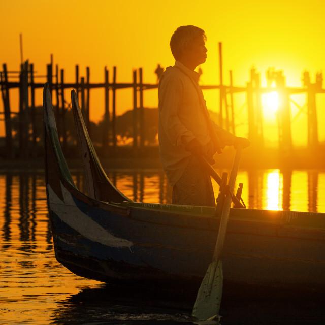 """Fishman under U bein bridge at sunset"" stock image"