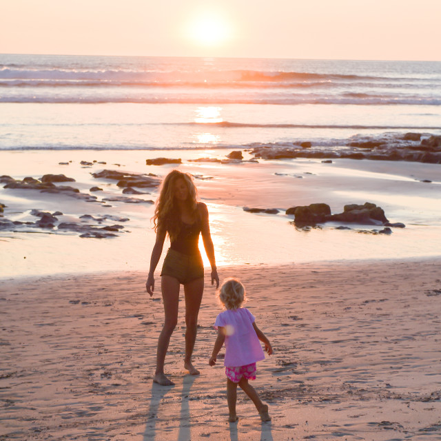 """Mum and Daughter Walking on Beach"" stock image"