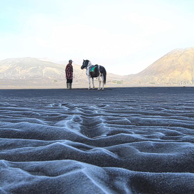 """frozen ice formation on the sand texture with a horseman and his horse"" stock image"