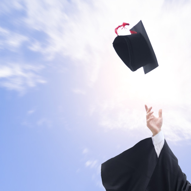 """""""Graduates throwing graduation hats in the air"""" stock image"""