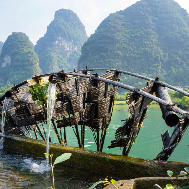 """Old wooden water mill in Yangshuo Li river"" stock image"