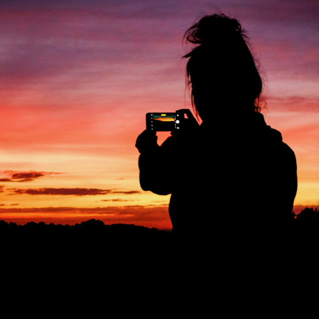 """Young woman photographs sunset on smartphone"" stock image"