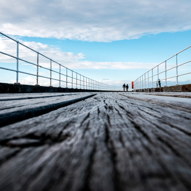 """Low angle shot of wooden pier with distant people"" stock image"