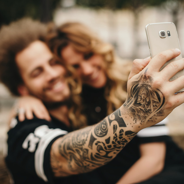 """Focus on tattooed arm of boyfriend making self-portrait of him and blonde girlfriend."" stock image"