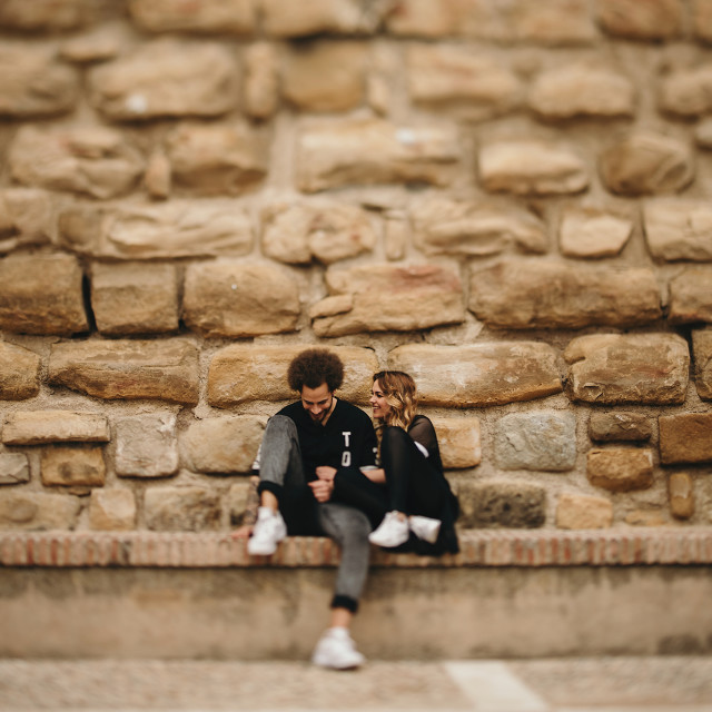 """""""Portrait of young couple sitting on long bench against of stone wall. Copyspace"""" stock image"""