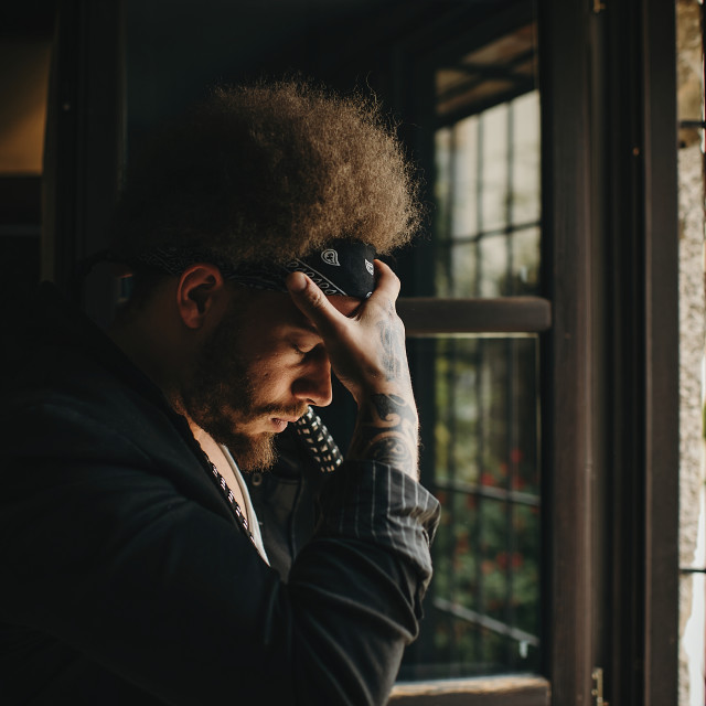 """Side view of pensive young bearded man with headband and afro holding hand on head with eyes closed. Stsnding at door in daylight"" stock image"