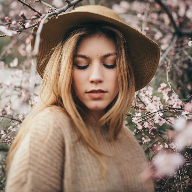 """Portrait of beautiful young girl with blonde hair in hat looking at camera with apple tree branches around"" stock image"