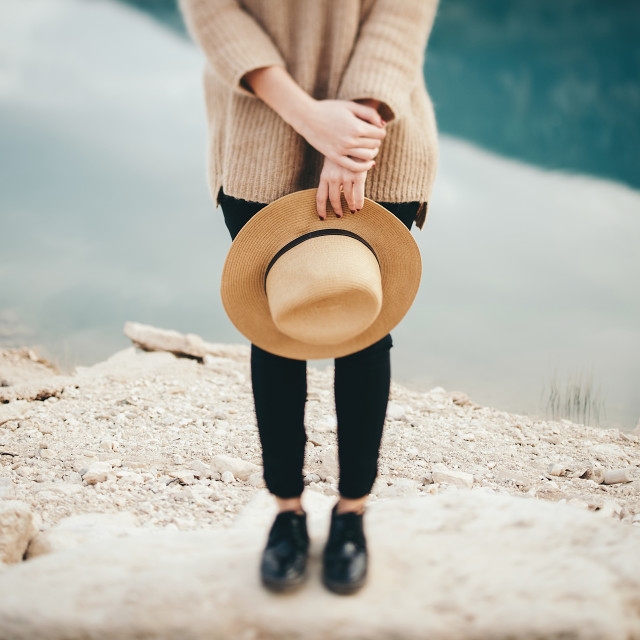 """Young girl is standing near water and holding a hat in hands."" stock image"