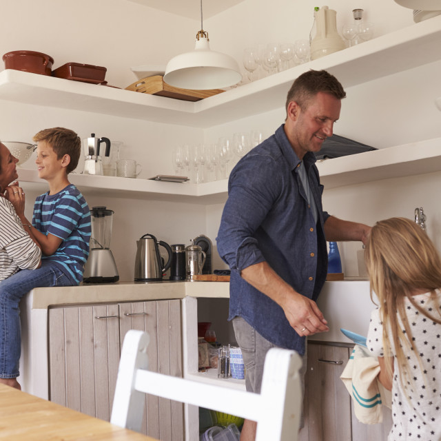"""Children Helping Parents In Kitchen With Chores"" stock image"