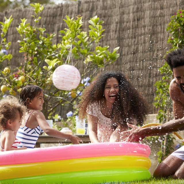 """Family Having Fun In Garden Paddling Pool"" stock image"