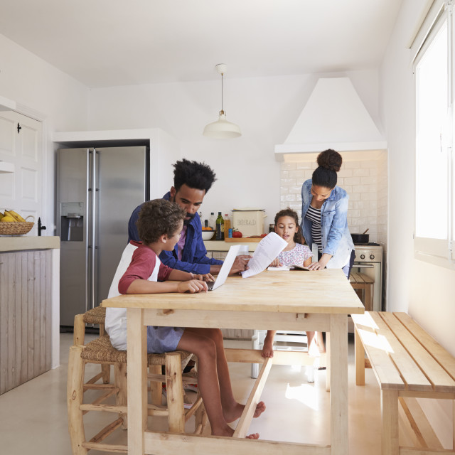 """Mum and dad help their kids with homework at kitchen table"" stock image"