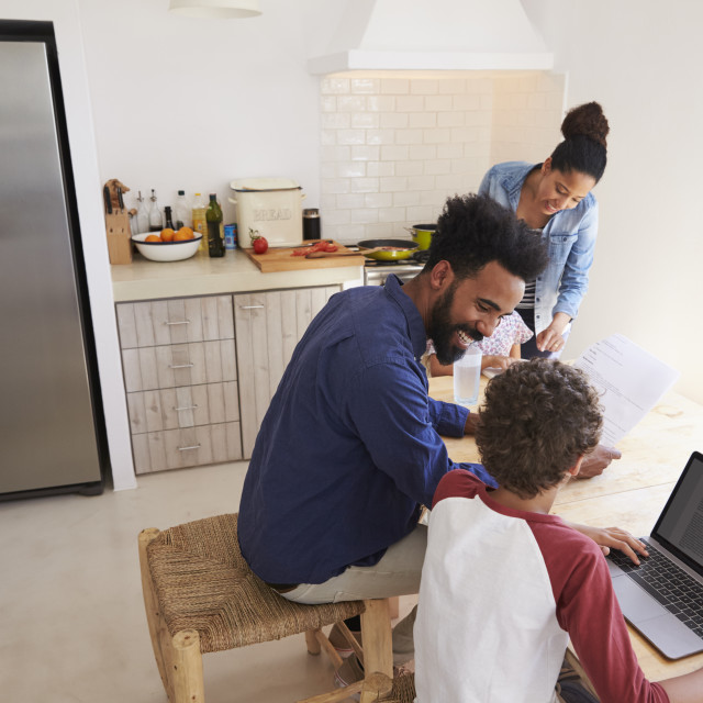 """""""Parents helping kids with homework in kitchen, elevated view"""" stock image"""