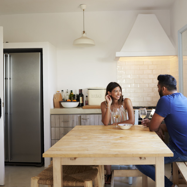 """Adult couple talk and drink wine in the kitchen, copy space"" stock image"