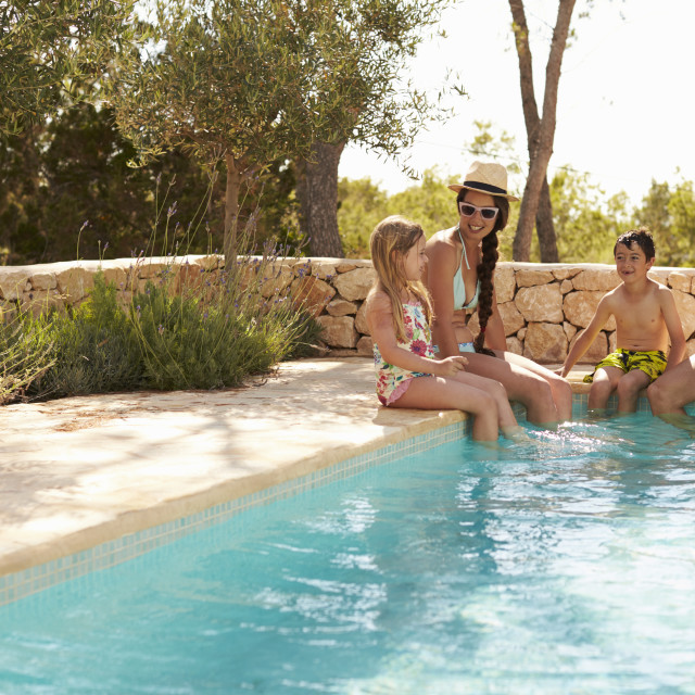"""""""Wide Angle View Of Family On Vacation Relaxing By Pool"""" stock image"""
