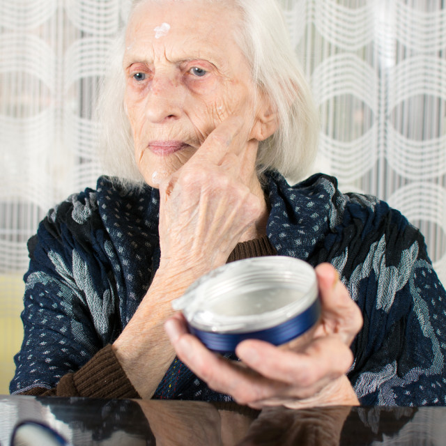 """Senior woman applying face cream"" stock image"