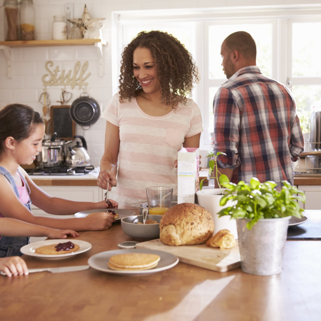 """""""Family At Home Eating Breakfast In Kitchen Together"""" stock image"""