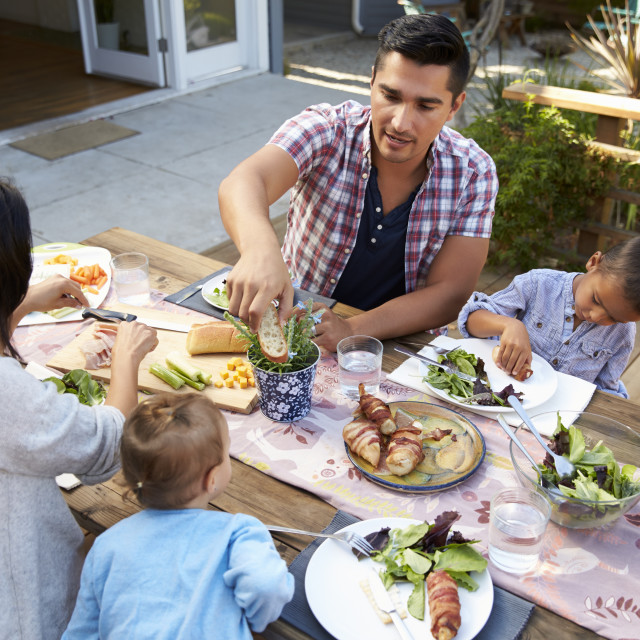 """""""Family At Home Eating Outdoor Meal In Garden Together"""" stock image"""