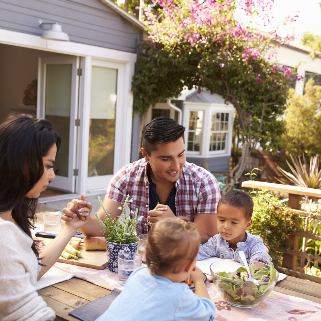 """""""Family Saying Grace Before Outdoor Meal In Garden"""" stock image"""