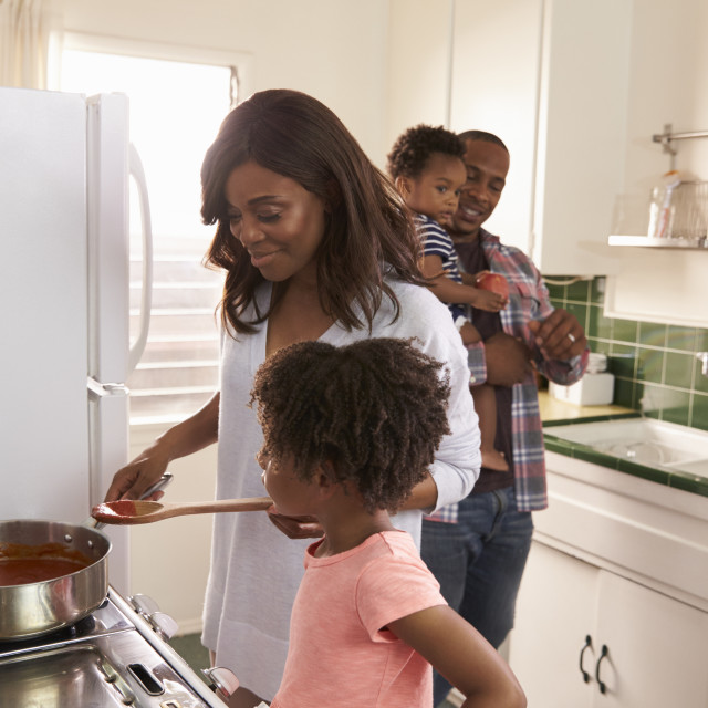 """""""Family At Home Preparing Meal In Kitchen Together"""" stock image"""