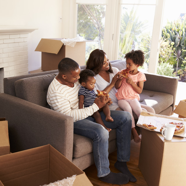 """""""Family Take A Break On Sofa With Pizza On Moving Day"""" stock image"""