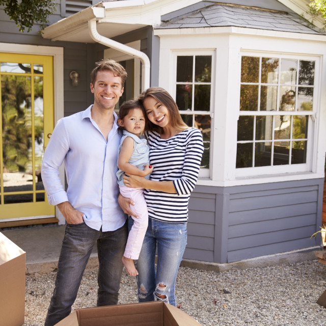 """""""Portrait Of Excited Family Standing Outside New Home"""" stock image"""