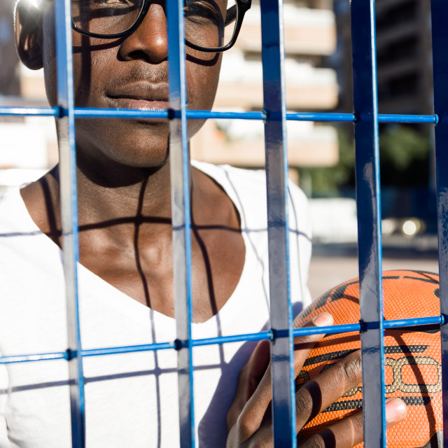 """Handsome young man playing basketball."" stock image"