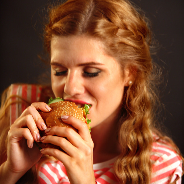 """Woman eating fast food . Girl enjoying delicious hamburger."" stock image"