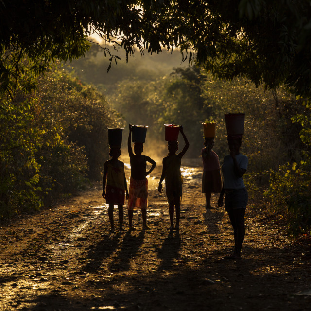 """Silhouette of woman carrying water and food on there head. Madagascar, Africa"" stock image"