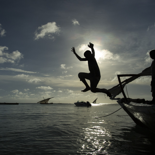 """Children jumping in water from the boat in Zanzibar, Tanzania"" stock image"