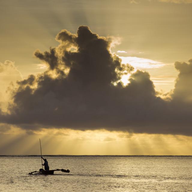 """Fisher man at sunrise on ocean going to fish in Zanzibar, Tanzania."" stock image"