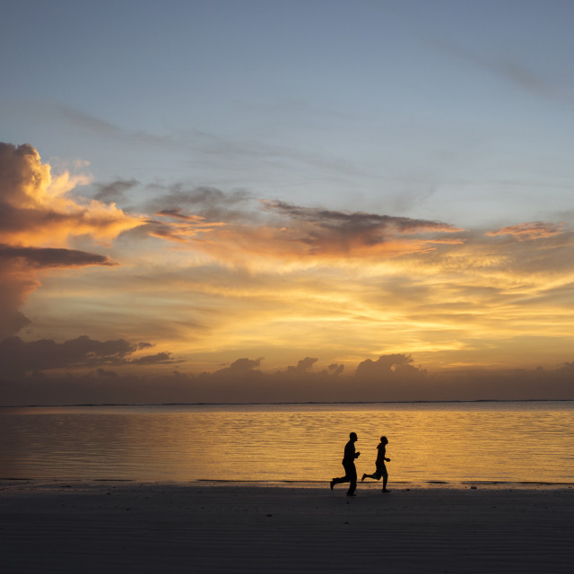 """Silhouette of two people jogging on beach at sunrise"" stock image"