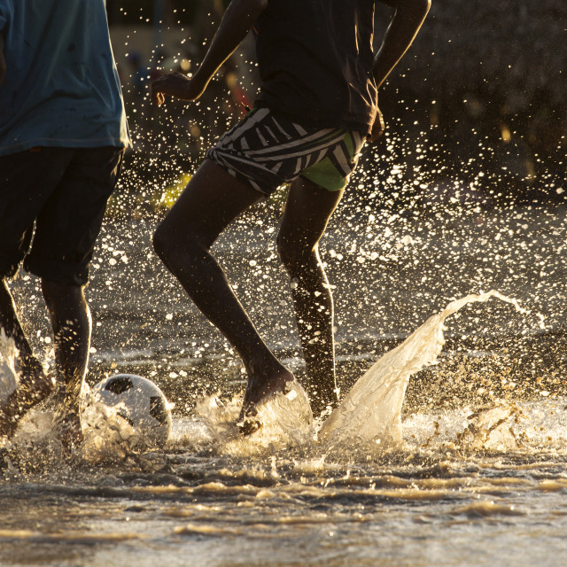 """Legs of black children playing footbal in water at sunset"" stock image"