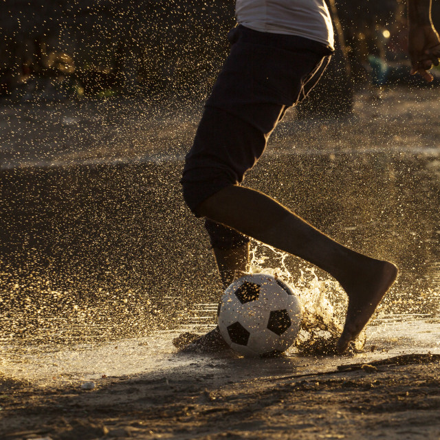"""Legs of a black child playing footbal in water at sunset"" stock image"