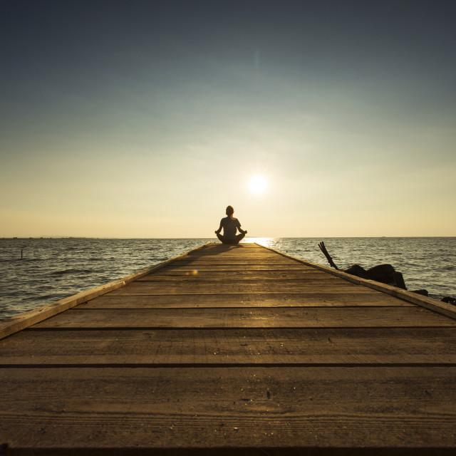 """""""Joyful man meditating on pontoon over a lake at sunrise"""" stock image"""