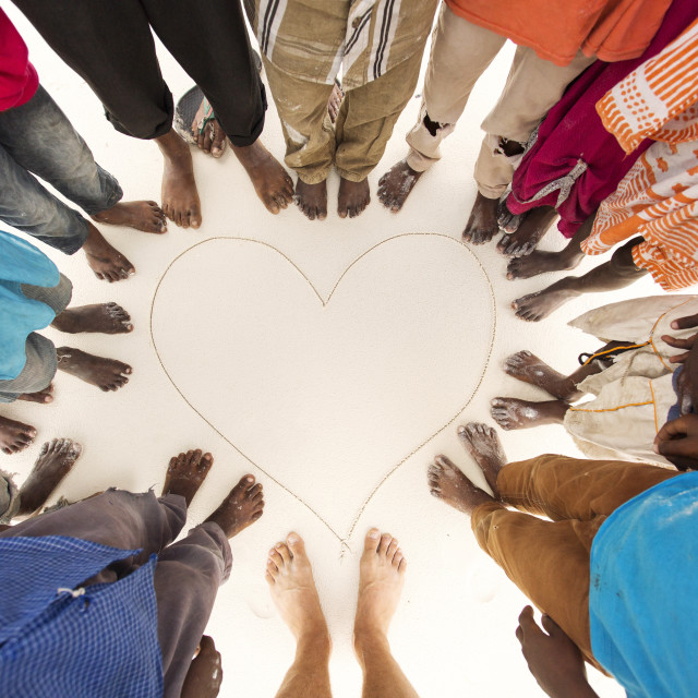 """Feet of black children on sands in Africa around a heart paint on sands"" stock image"