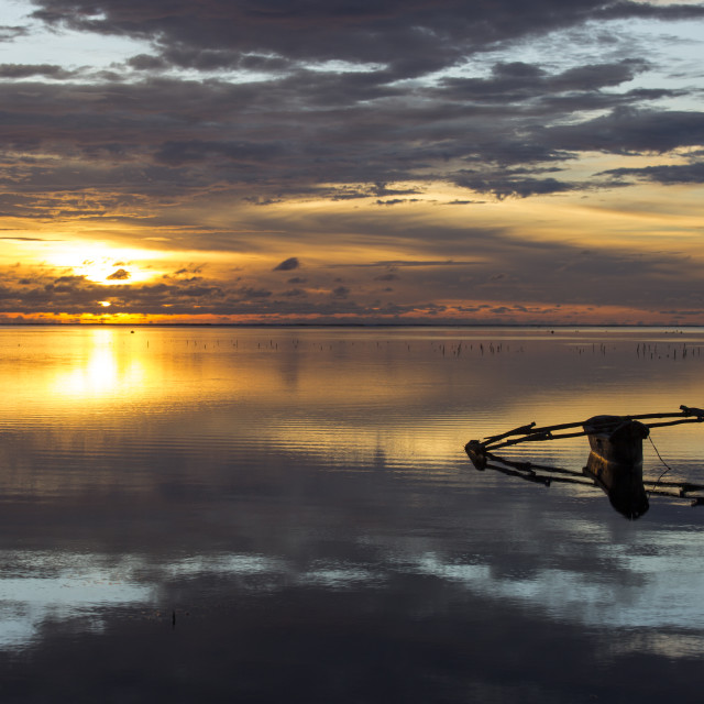 """""""Traditional fishing boat in Zanzibar with storm clouds at sunrise"""" stock image"""