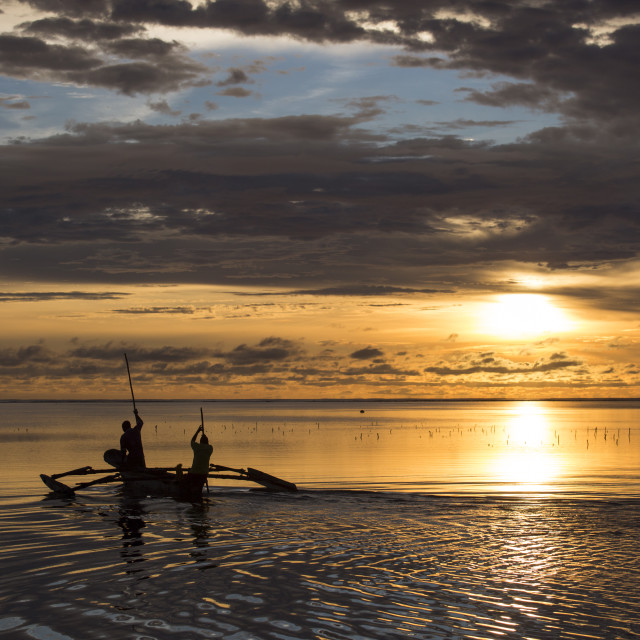"""Fishermen going on ocean on traditional fishing boat in Zanzibar with storm..."" stock image"