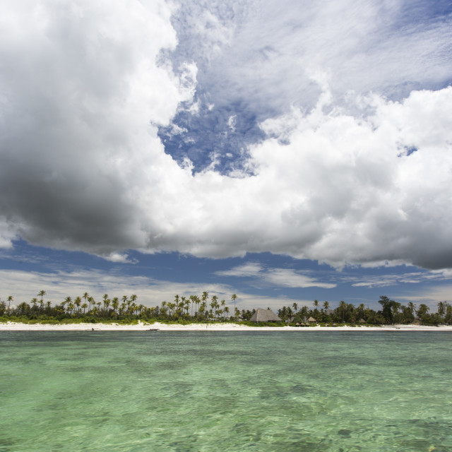 """Beach of Zanzibar with white clouds and colorful water"" stock image"