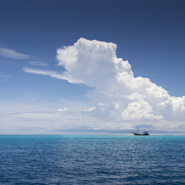 """Traditional fishing boat in Zanzibar with white clouds and blue water and sky"" stock image"