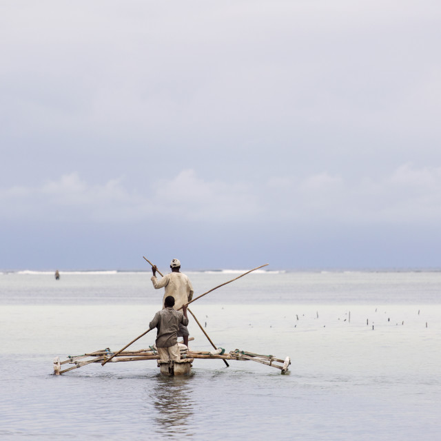"""Fisherman in Zanzibar going to fish in morning with storm clouds"" stock image"