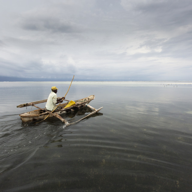 """Fisherman going to fish in Zanzibar at morning with storm clouds"" stock image"