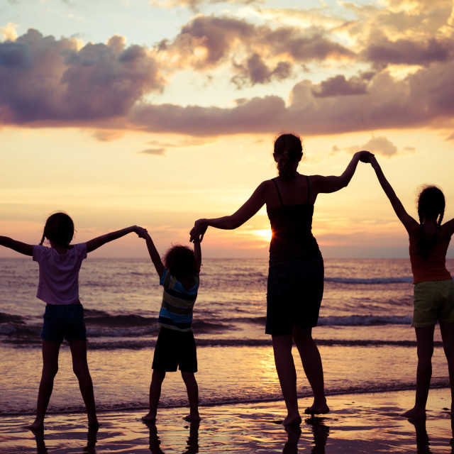 """""""Mother and children playing on the beach at the sunset time."""" stock image"""
