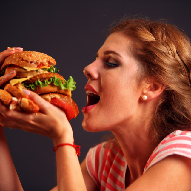 """Girl opened her mouth, holding a hamburger on his outstretched hands and..."" stock image"