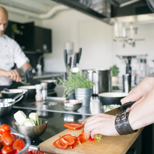 """""""Close-up of student cutting pepper on board"""" stock image"""