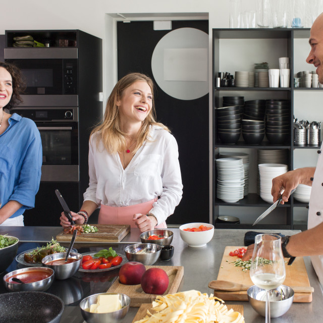 """""""Chef smiling with two students at table"""" stock image"""