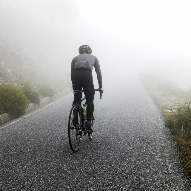 """a cyclist rides into the fog"" stock image"