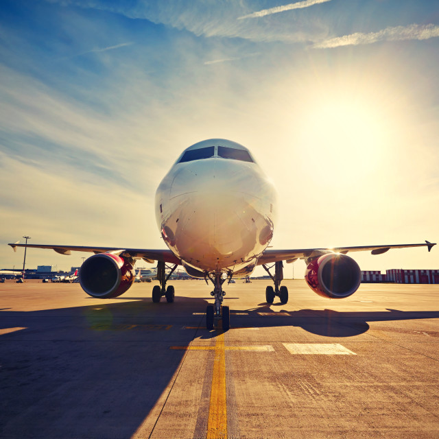 """Airplane is taxiing to take off at the sunrise"" stock image"