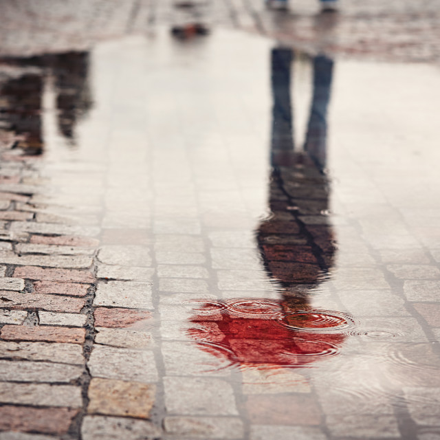 """Rainy day. Reflection of young man with red umbrella in puddle on the city street during rain."" stock image"